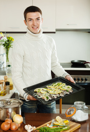panful: Handsome man with raw fish on roasting pan