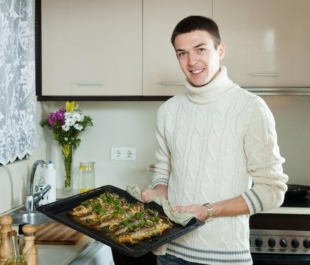 pesce cotto: Uomo sorridente con pesce cotto in padella