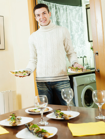 pesce cotto: Bel ragazzo che serve tavolo di festa con pesce cotto