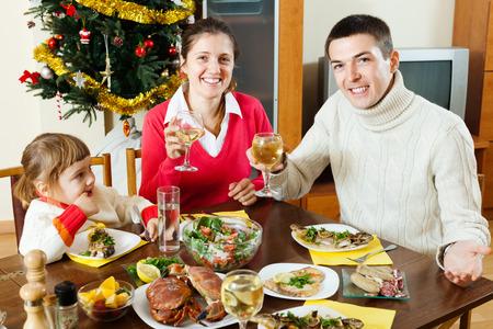 Happy family of three celebrating Christmas  over celebratory table  photo