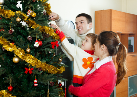 decorating christmas tree: Parents and baby girl decorating Christmas tree at  home Stock Photo