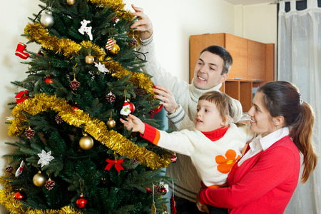 men and his wife  and baby girl preparing for  Christmas at home photo