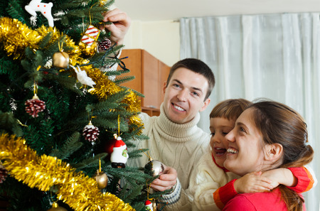 home decorating: Happy parents and baby girl decorating Christmas tree at  home