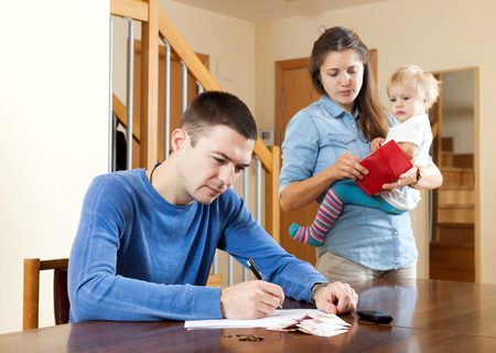parsimony: Financial problems in family. Sad woman with baby against husband at table with money Stock Photo