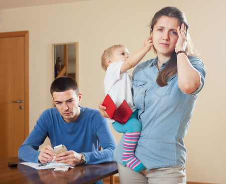 Man and wife  with baby having  financial problems at home photo