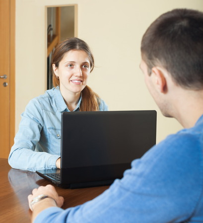 Guy talking with employee with laptop in home