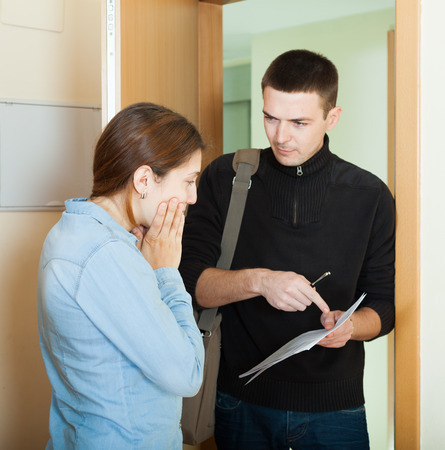 rapacity: businessman trying to collect money from housewife at home door. Focus on woman Stock Photo