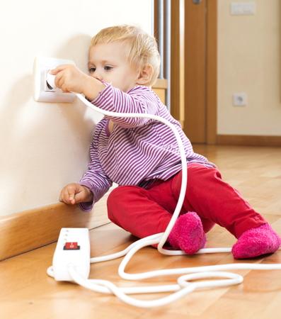 Bebé que juega con la extensión eléctrica y la salida en el hogar