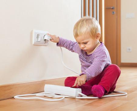 Bebé que juega con extensión eléctrica en el piso en casa