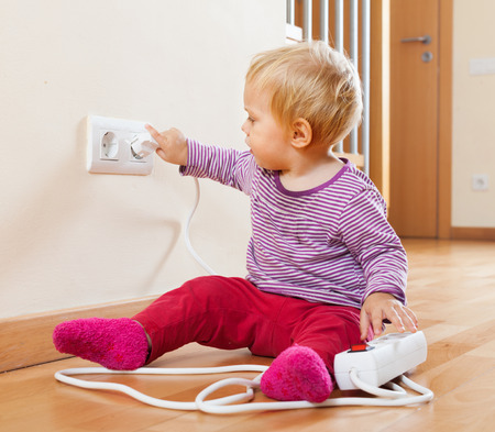 Toddler playing with extension cord and outlet at home