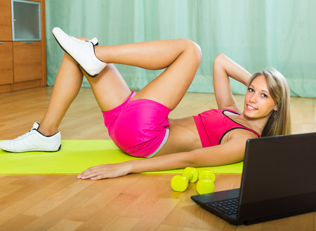 house trained: Positive young woman working out with notebook in gym