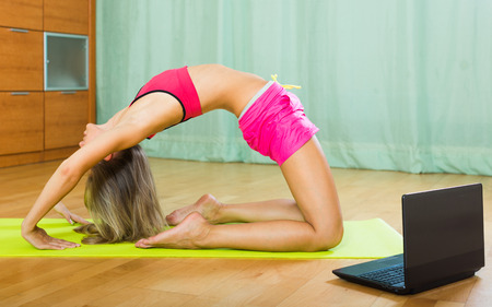 house trained: Long-haired young female having pilates class with notebook at home
