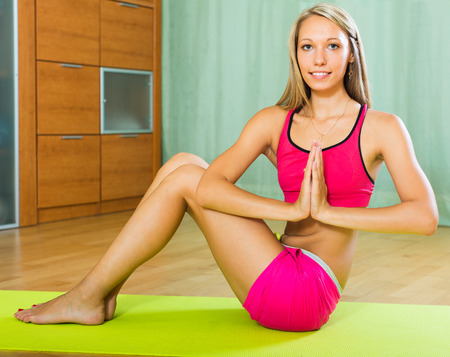 house trained: Happy slender sporty girl doing yoga at home and smiling