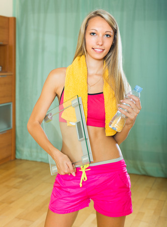 weigher: Cheerful smiling girl with weigher after morning exercises