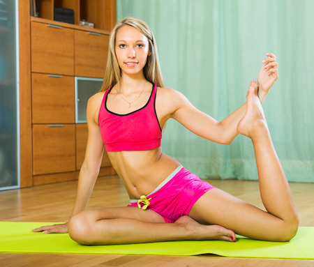 perspire: Attractive long-haired young woman having pilates class indoor