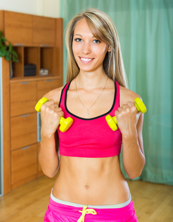house trained: Happy smiling young female training with dumbbells at home