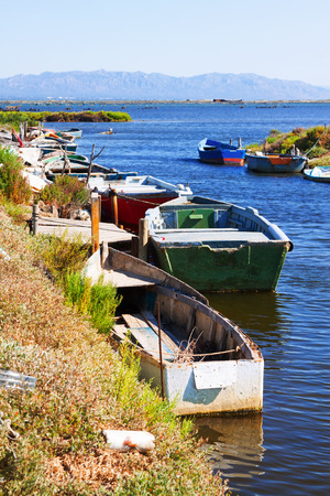 ebre: Old fishing boats at delta of Ebro river in summer day. Catalonia, Spain Stock Photo