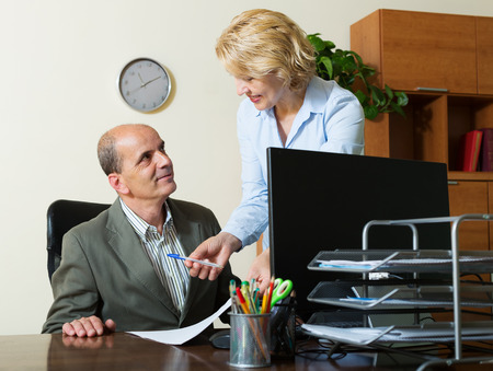 office scene: office scene with two mature and positive co-workers  Stock Photo