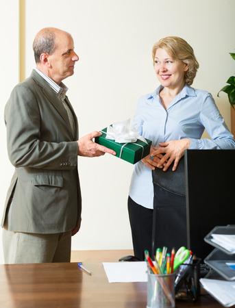 Elderly man congratulating colleague on her birthday in office photo