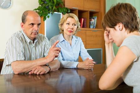 Mature parents berating adult daughter in home interior  Stock Photo