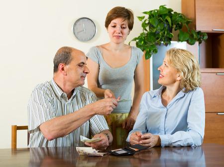bolsa dinero: Hija adulta pidiendo a los padres de pensionistas por dinero en casa Foto de archivo