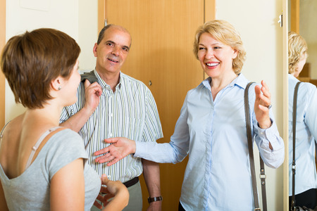 Young woman meeting mature friends at the door  Stock Photo