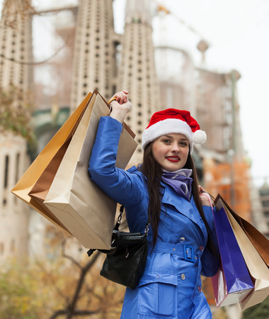 Smiling girl with shopping bags against Sagrada familia during the Christmas sales at Barcelona