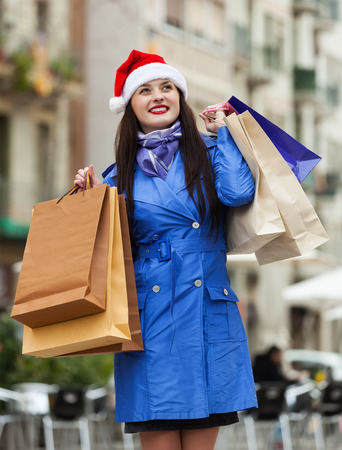 Smiling woman with shopping bags at street during the Christmas sales photo