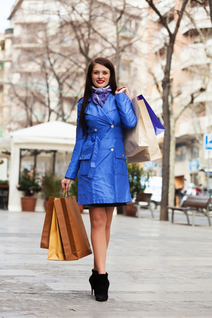 Happy girl with shopping bags at street photo