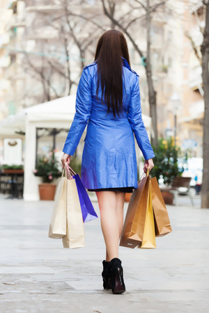 Rear view of woman in blue cloak with shopping bags photo