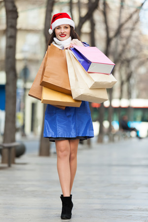 Young girl in coat  with shopping bags at street during the Christmas sales photo