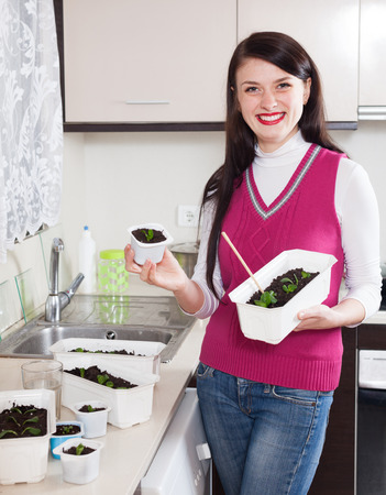 Happy woman with various seedlings at home kitchen photo