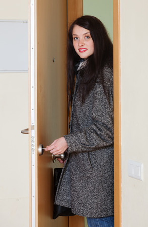 enters: Woman in coat unlocking the door and enters the house Stock Photo