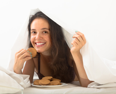 Brunette girl eating chocolate chip cookies in her bed and smiling photo