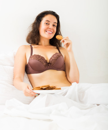 Young woman eating sweet cookies on white sheet in bed photo