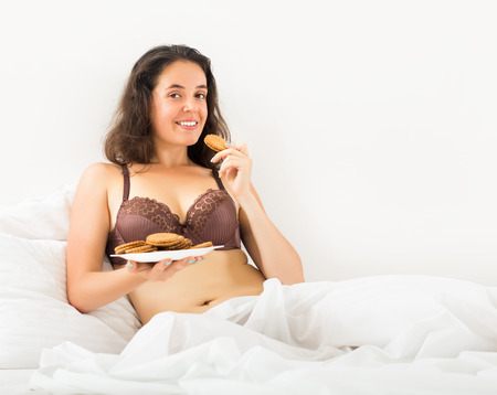Long-haired woman eating  chocolate chip cookies in bed     photo