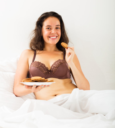 Brunette young girl eating sweet cookies in bed photo
