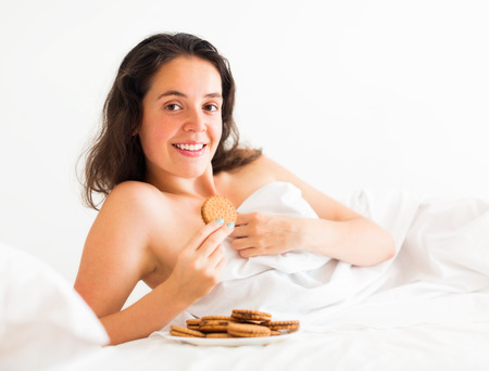 Beautiful young girl eating sweet cookies in bed photo