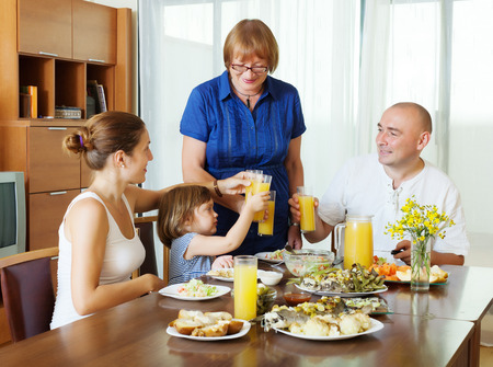 celebratory:  three generations family together around festive table at home