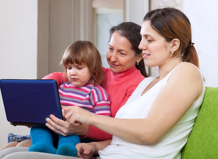 Happy women of three generations sits on sofa in livingroom with netbook  photo