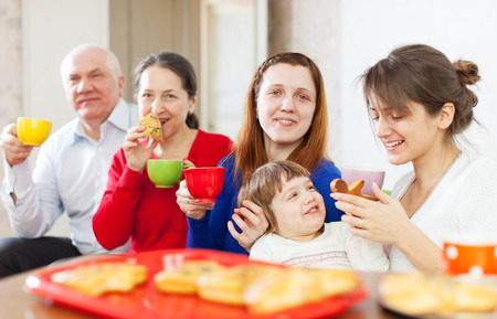 cooky:  family having tea with cakes at home  together Stock Photo