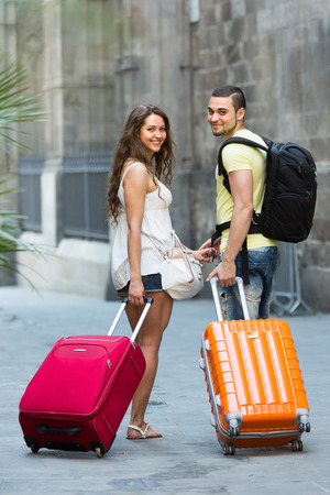 Positive smiling tourist couple with baggage heading to hotel on foot  photo