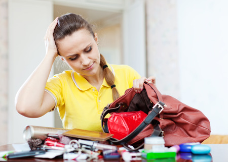 reticule: Upset inconsiderate woman lost something  in her purse Stock Photo
