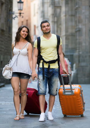 Man and woman in shorts with luggage walking through city street photo