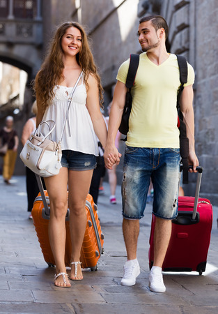 Young couple in shorts with luggage walking through city street photo