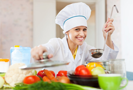 Happy professional cook in white workwear works in commercial kitchen photo