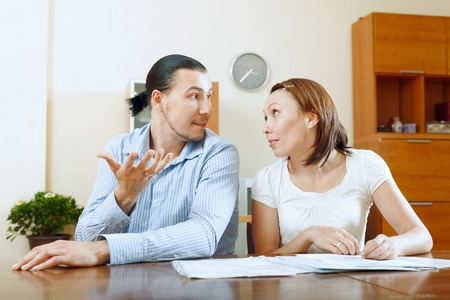 rapacity: Adult man and woman having quarrel about documents  Stock Photo