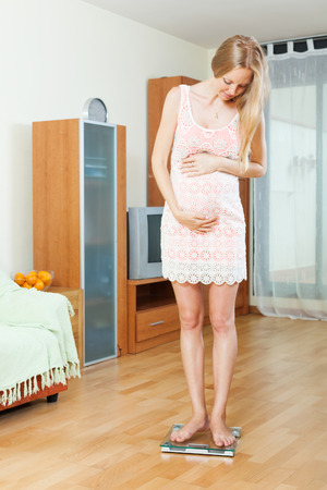 underweight: pregnancy woman standing on bathroom scales at home interior