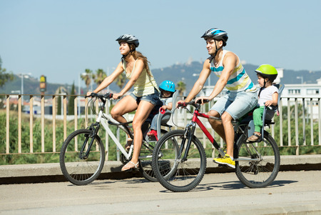 Sporting young father, mother and two children in baby bicycle seats summer day Standard-Bild