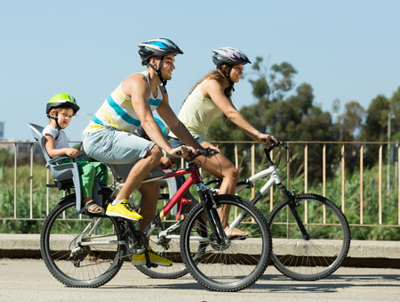 Active young family with two little daughters traveling by bicycles. Focus on man 스톡 콘텐츠